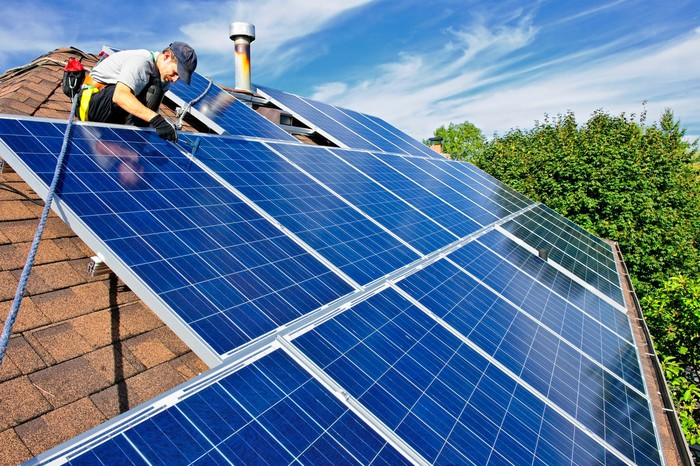 Solar panel installer puts panels on a roof.