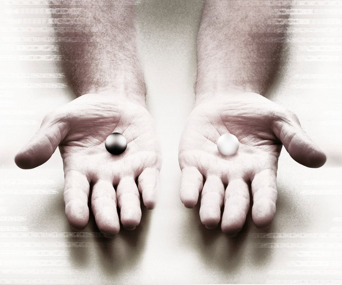 Two hands holding different-colored marbles