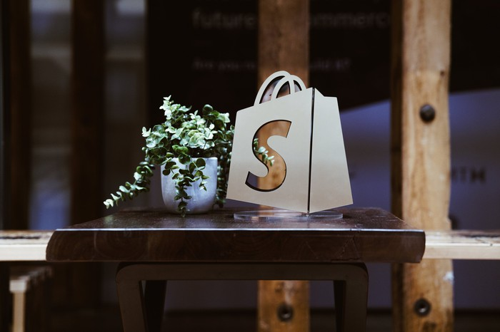 The Shopify logo on a bag, which is sitting on a table next to a plant.