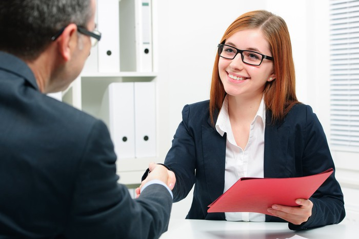 Professionally dressed woman holding red folder shaking hands with professionally dressed man seated across from her
