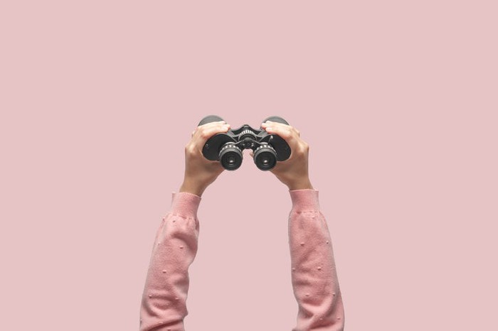 A pair of hands holding up a pair of binoculars.