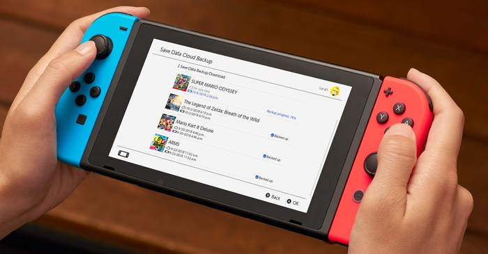 Close-up of a person's hands holding a Nintendo Switch game system.