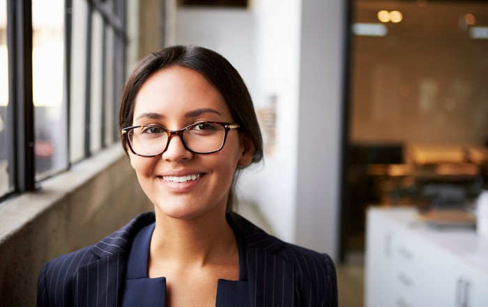 A smiling young professionally dressed woman in glasses