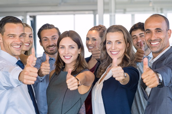 A group of businesspeople with their thumbs up