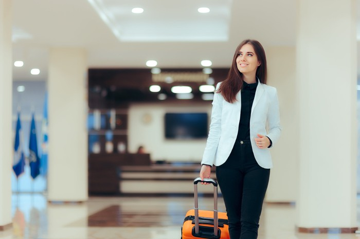 A businesswoman walks through a sparkling hotel lobby pulling a wheeled suitcase.