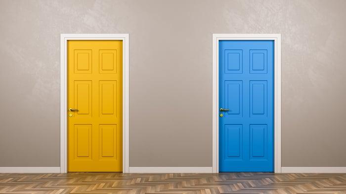 One yellow door and one blue door next to each other.