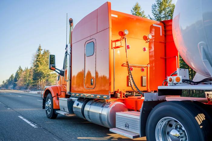 Big orange semi truck hauling a tanker of liquified gas.