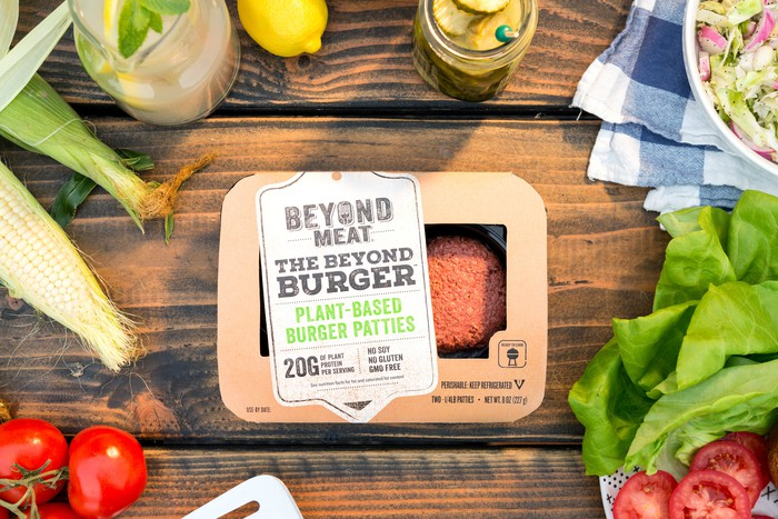 A package of Beyond Meat burgers on a picnic table surrounded by condiments and fixings.
