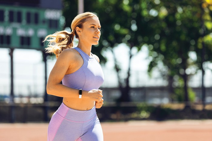 A woman wearing a Fitbit device while jogging.