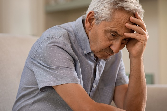 A concerned looking senior man hunches over and holds his head