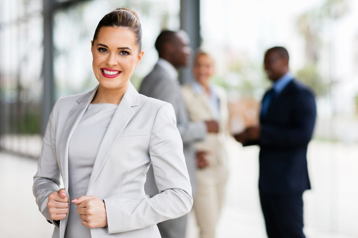 Smiling woman in business suit with a group of professionals blurred in the background