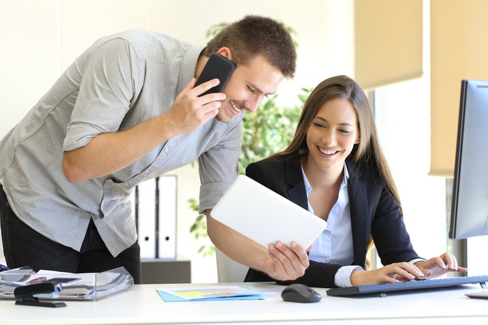 Two young professionals doing business together, sharing a phone and a computer.