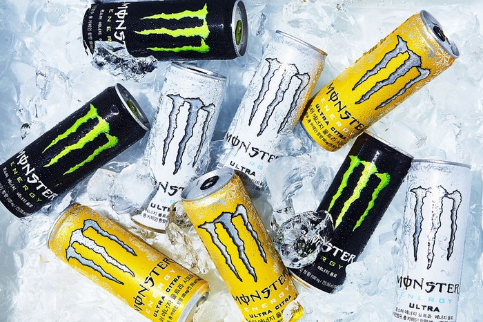 Nine Monster Energy cans in black, white, and yellow, on ice.
