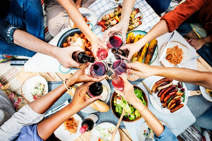 A group of friends clink their drinks together over a big meal.