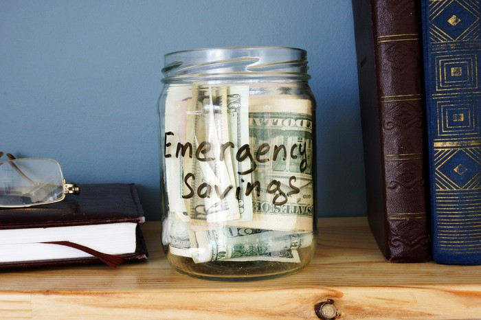 A glass jar filled with cash and labeled emergency savings sits on a wooden shelf, between books and a pair of reading glasses.