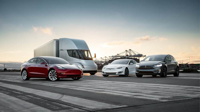 Tesla vehicles, including the Model 3, Tesla Semi, Model S, and Model X, in a parking lot.
