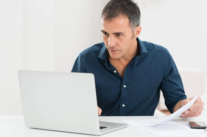 A man sits looking at a laptop monitor, while holding a document in one hand.
