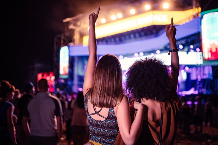 Cropped shot of two young female friends dancing at a music festival.