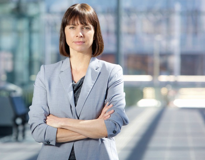 Woman in business suit with serious expression and crossed arms.