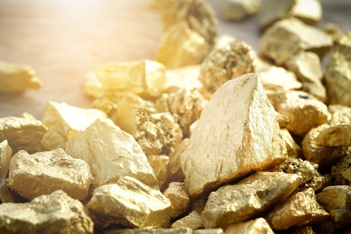 A pile of gold nuggets on a flat surface