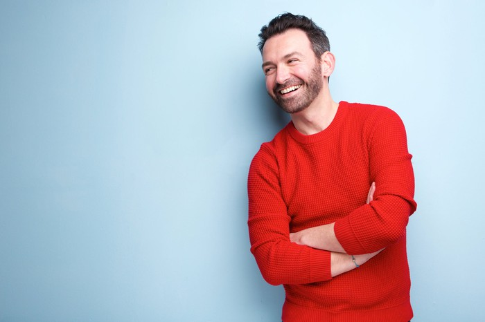 Smiling younger man in red shirt with arms crossed against blue background