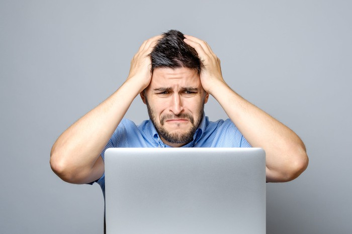 Man at laptop with sad expression holding his head with both hands