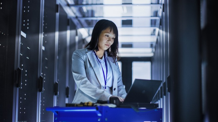 A computer scientist amid mainframes looks at her laptop