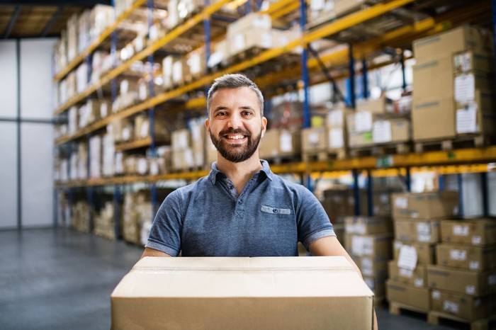A smiling worker in a warehouse holds a box