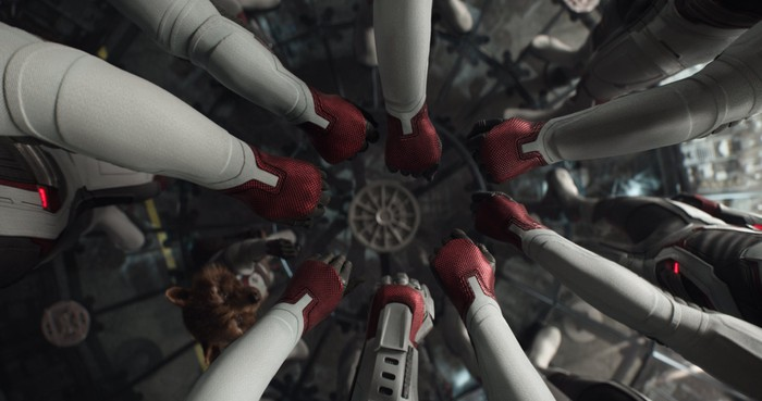 The Avengers put their hands in a circle, while Rocket Raccoon reaches up to join them, in a scene from Avengers: Endgame.