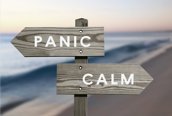 """A wooden beach sign pointing in two directions: """"Panic"""" and """"Calm."""""""