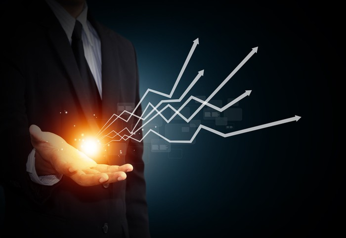 A man in a business suit holds out his hand where there is a spark of light and upward-sloping lines emanating from it.