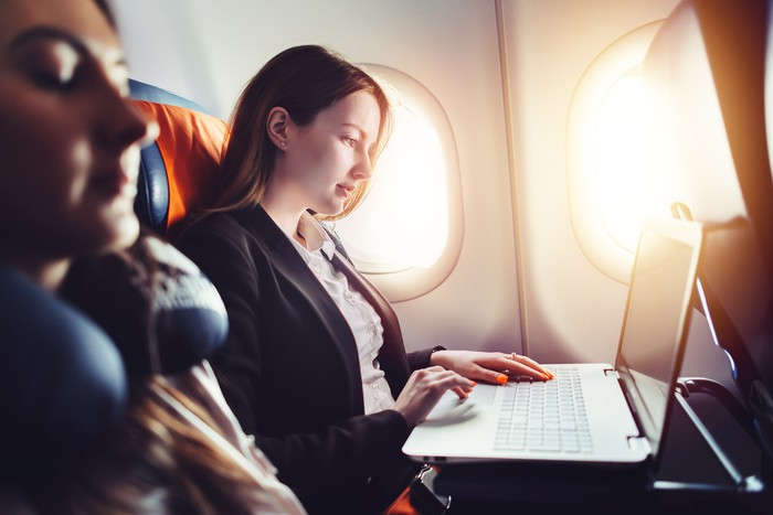 Professionally dressed woman in airplane window seat typing on laptop while female passenger next to her sleeps