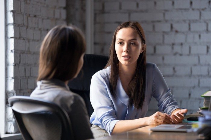Professionally dressed woman with serious expression talking to another woman.