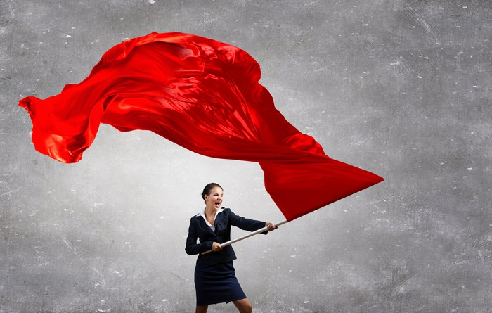A businesswoman waves a red flag.