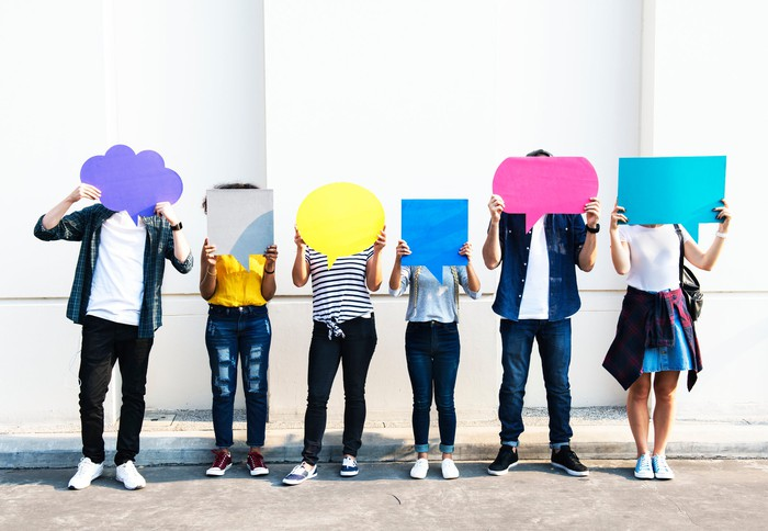 Teens holding cardboard speech bubbles.