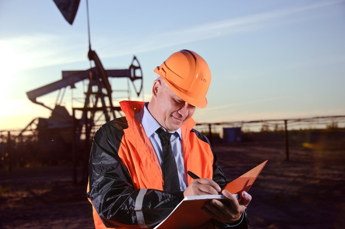 A man wearing an orange hard hat writing in a notebook with an oil well in the background.