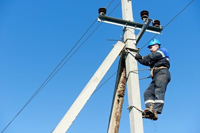 A man working on an overhead power line.