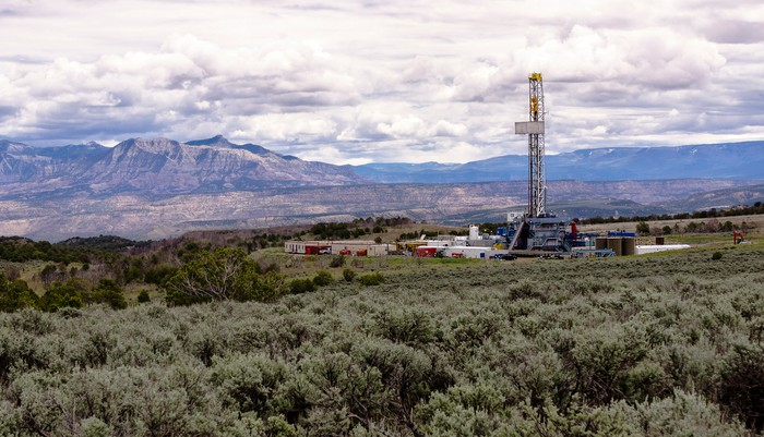 A drilling rig with the mountains in the background.