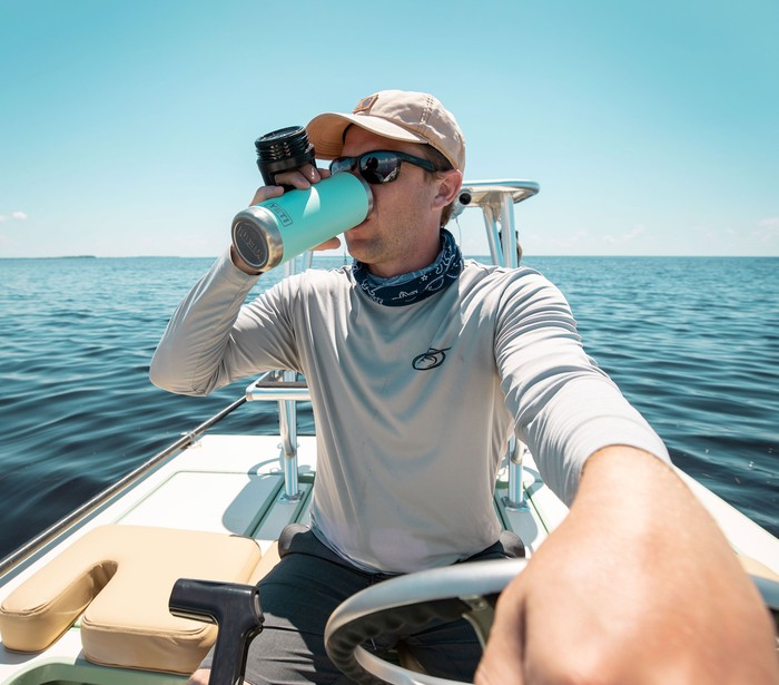 Man drinking from Yeti insulated mug while on a boat
