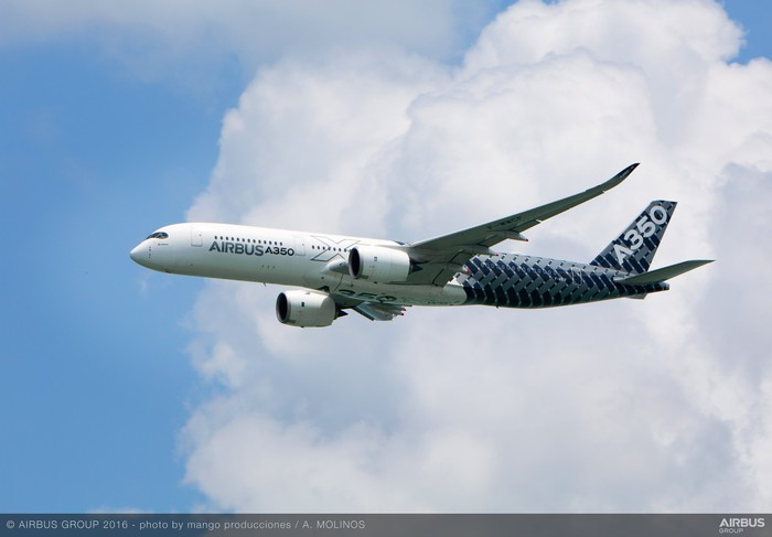 An Airbus A350 flying in front of a cloud.