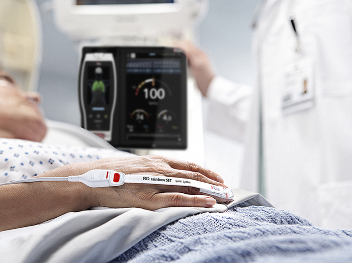 Patient in hospital bed with a Masimo pulse oximeter next to them.