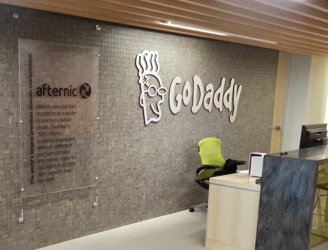 A white GoDaddy logo on a dappled grey office wall.