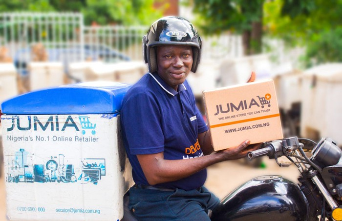Jumia delivery driver on a motorcycle with a box with the Jumia logo.