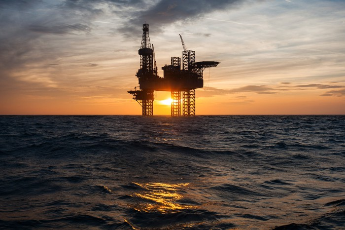 Silhouette of an offshore oil drilling rig with the sun setting in the background.