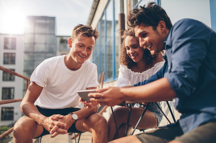 Three people all gathered around looking at a smartphone.