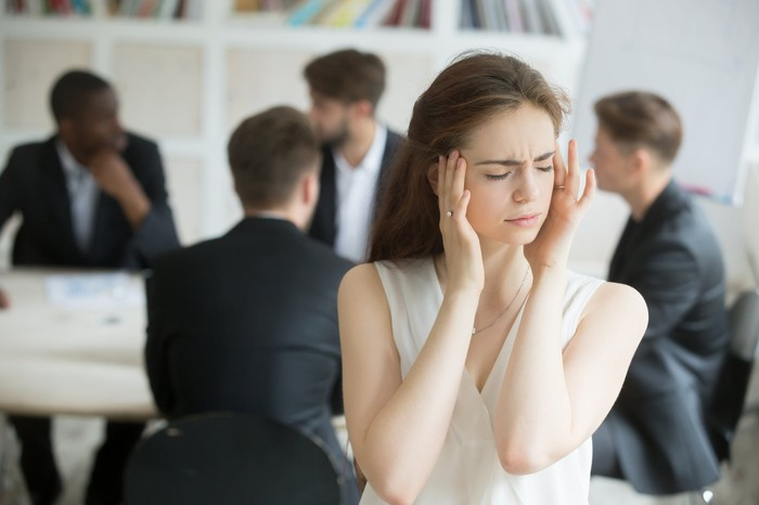 Woman plugging ears with fingers in front of table of men in suits