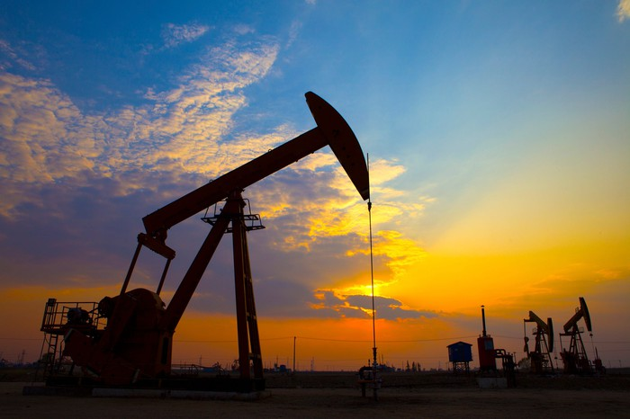 Oil pumps with the sun setting in the background.