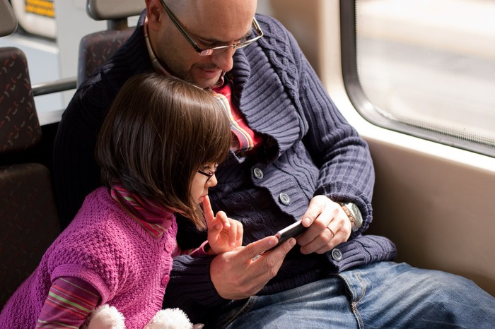 A father and daughter watch video on a smartphone.
