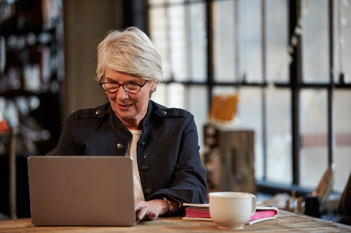 Older woman typing on laptop; next to laptop are a mug and book