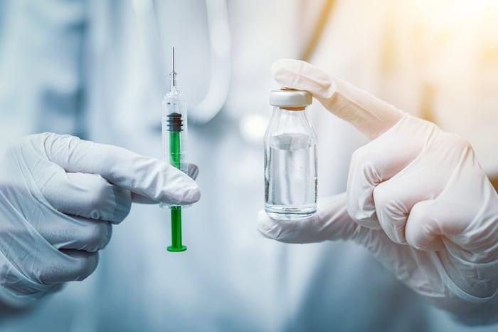 Gloved hands holding a syringe and a vial of medicine